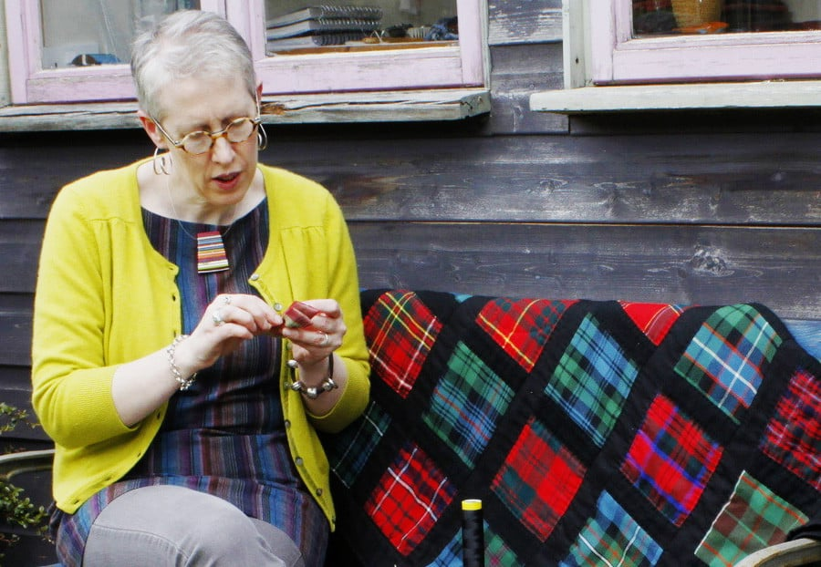 A lady sewing a quilt