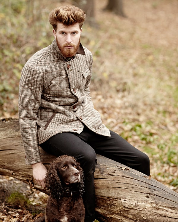 Man modelling a jacket with a dog by his side