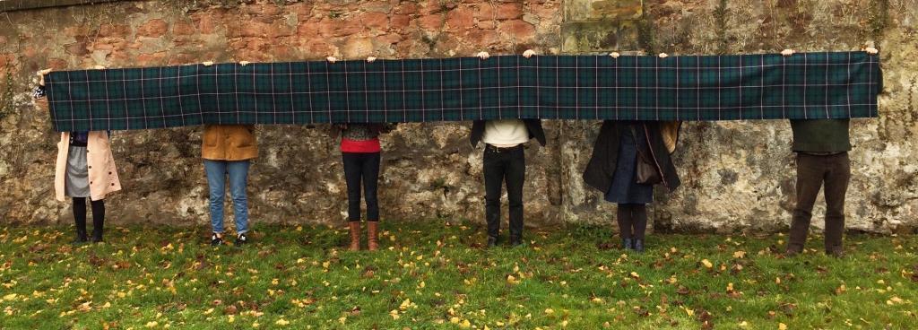 People holding tartan fabric