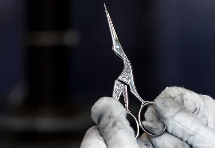 Workers hands holding up a pair of Ernest Wright Antique Stork scissors for inspection