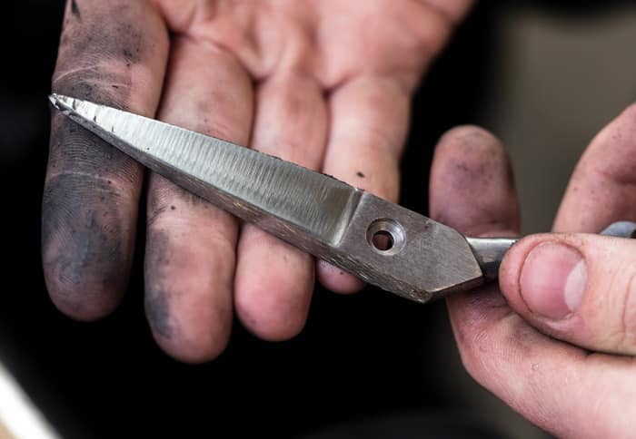 Workers hands holding a single blade before polishing