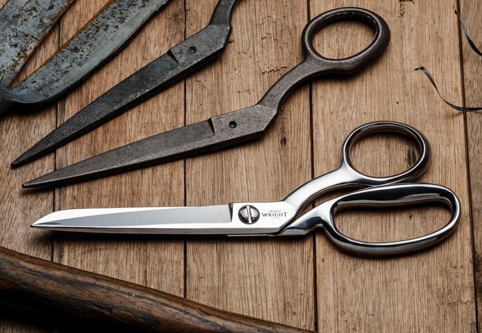 "A pair of Ernest Wright Dressmaker Shear 8.25"" lying on top of a table with a selection of scissors"