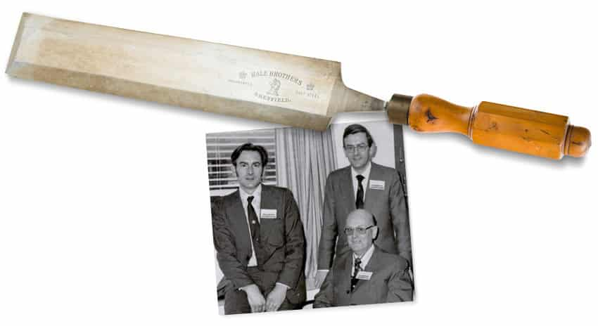 Black and white photo of three gentlemen in suits with a chisel laying over the edge of the image