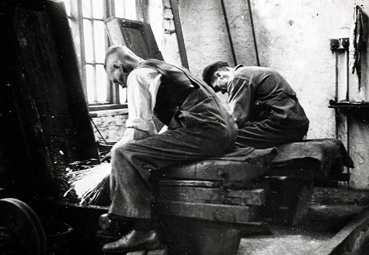 Black and white image of two men working at the grind stones