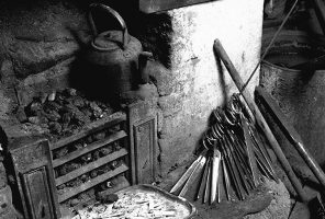 Very old image of an open coal fire grate with scissors bunched together ready to be worked on