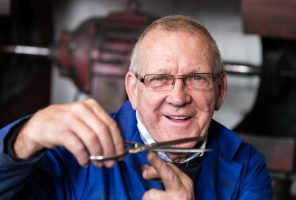 Ernest Wright employee holding a pair of scissors sideways to check the blades