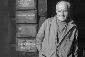 A black and white portrait of Frank Turton outside his factory